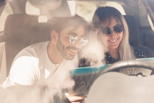Счастливая пара сидит в машине, глядя на карту