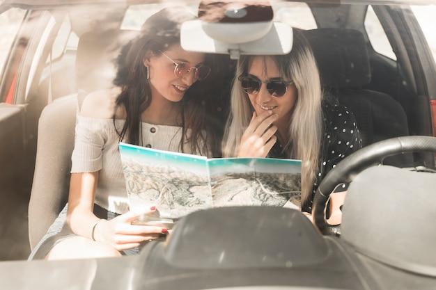 Женщины, сидящие в машине, ищущие направление на карте