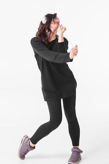 白い背景で隔離されたヘッドフォンダンスを着て女性ダンサー