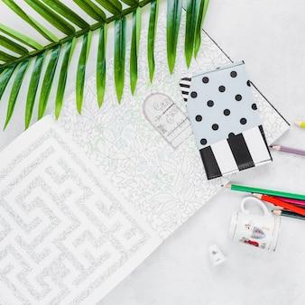 Крупный план лабиринта с кошельком, листом, цветным карандашом и чашкой