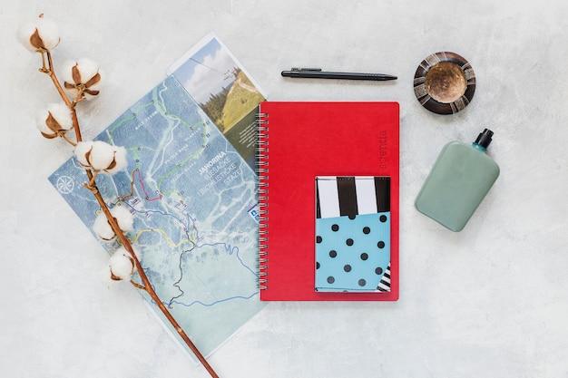 背景の地図、ノート、財布付きコットンの小枝