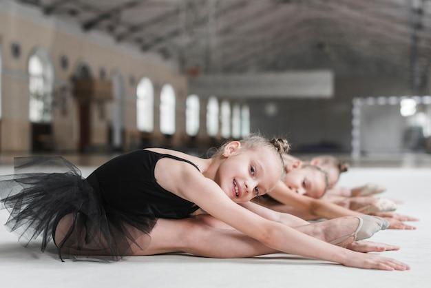 彼女の友人と一緒に前に伸びている床に座っている女の子