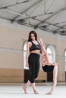 バレエインストラクターは若い生徒の足を持って、バレエの姿勢で彼女を助けます。