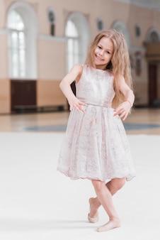 ダンスのクラスで踊っている笑顔のバレリーナの女の子
