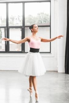 ダンスフロアの先端のつま先で踊るバレリーナダンサー