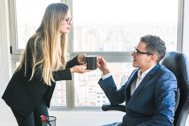 オフィスで彼女の上司にコーヒーを与えるビジネスマン