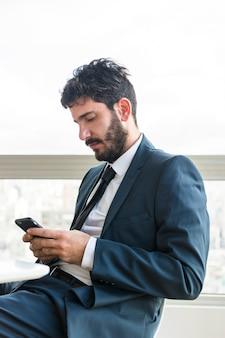 携帯電話を使用してオフィスに座っている若い実業家