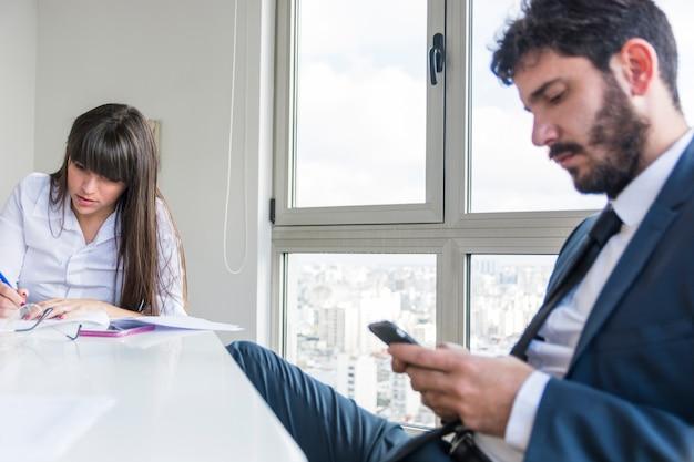 デジタルタブレットを使用して男性とオフィスで働く実業家