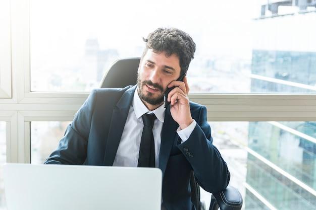 Портрет молодой предприниматель, говорить на мобильном телефоне у окна