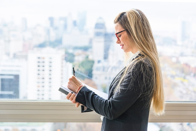 Улыбается блондинка молодая женщина, писать в документе с ручкой
