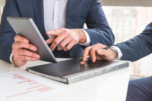 デジタル、タブレット、財務報告書を議論するビジネスマンのクローズアップ