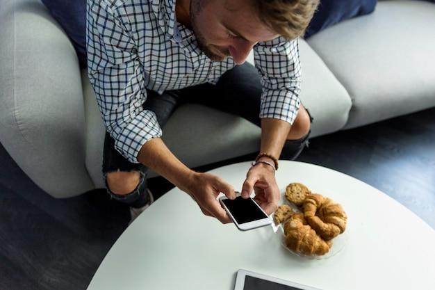 スマートフォンで働く若い男