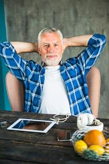 机の上にデジタルタブレットと携帯電話を持つ上級男の肖像