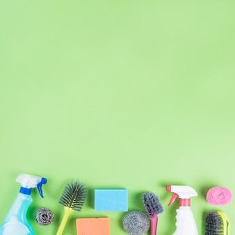 緑の背景の端にある様々なクリーニング製品