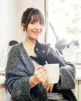 彼女の猫を保持しているコーヒーのカップを持つ幸せな女性