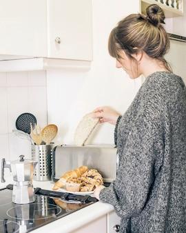 トースター、パンを入れている女性