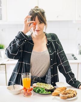Портрет женщины, держащей помидор черри перед ее глазами