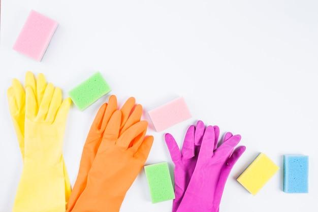Красочные перчатки и губки на белом фоне