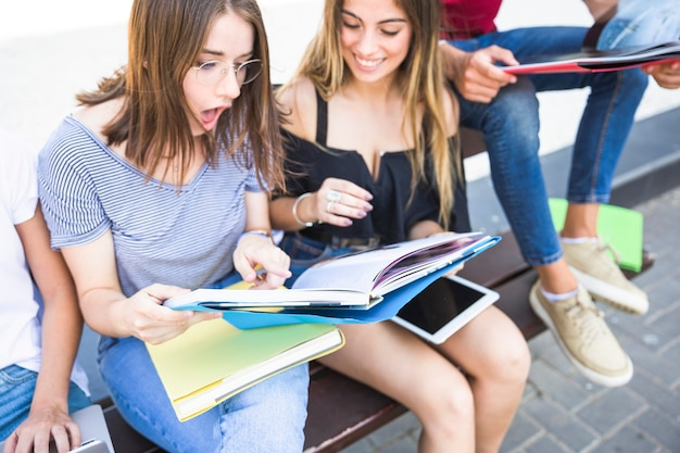ショックを受けた女性が教科書を友人と読む