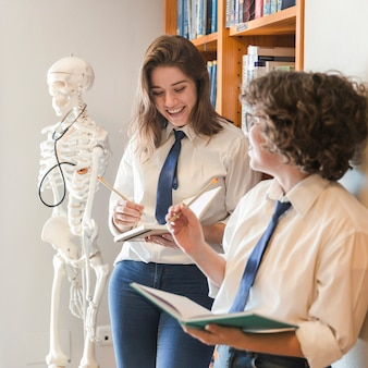 Веселые подростки, обучающиеся в библиотеке