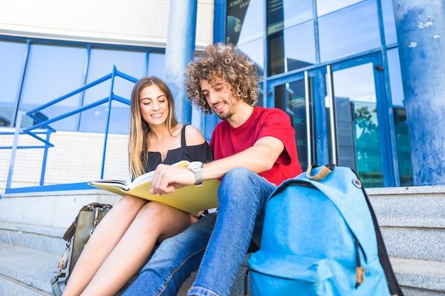 大学外で勉強する笑顔のカップル