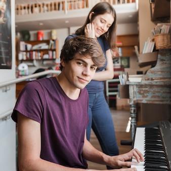 居心地の良い部屋のガールフレンドのためにピアノを弾くティーンボーイ