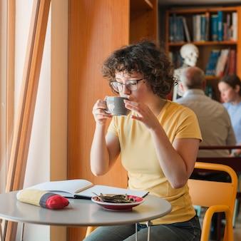 勉強中に飲み物を飲む女性の十代