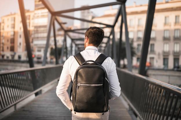 Вид сзади человека с черным рюкзаком, стоящим на мосту