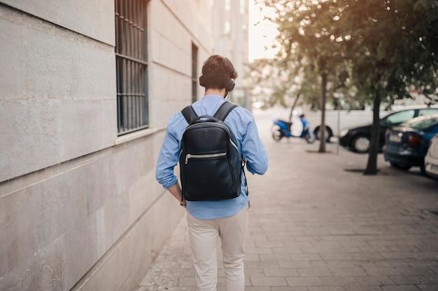 舗装の上を歩く黒のリュックサックを持つ男の背面図