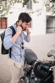 彼のバイクの近くに若い男性観光立っている