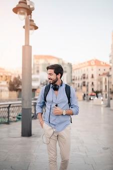 Улыбающийся мужской турист, идущий по тротуару