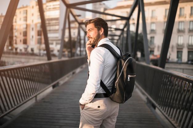 橋に乗った男性観光客のリアビュー