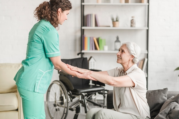 Женщина-медсестра, держащая за руки старшая женщина-инвалид