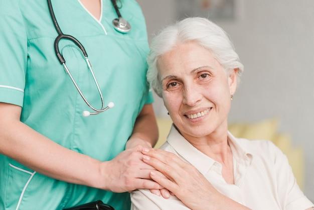 肩に看護師の手に触れる笑顔のシニア女性