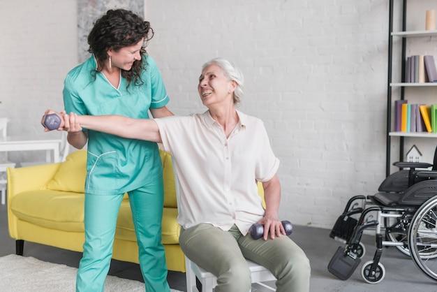 女子理学療法士との高齢女性訓練のクローズアップ