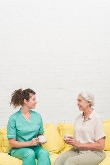 笑顔の女性の看護婦とシニアの女性は、お互いを見てコーヒーカップを保持