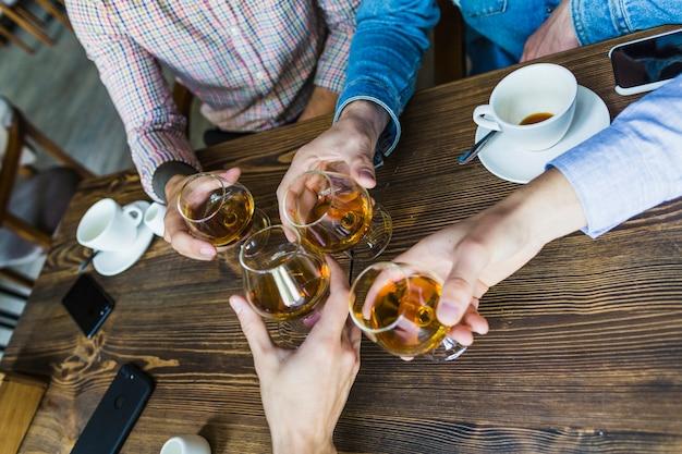 クローズアップ、男性、手、飲みながら、飲み物、木製、テーブル