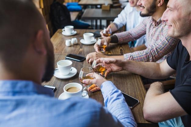 彼の友人と座って飲み物を楽しんでいる男