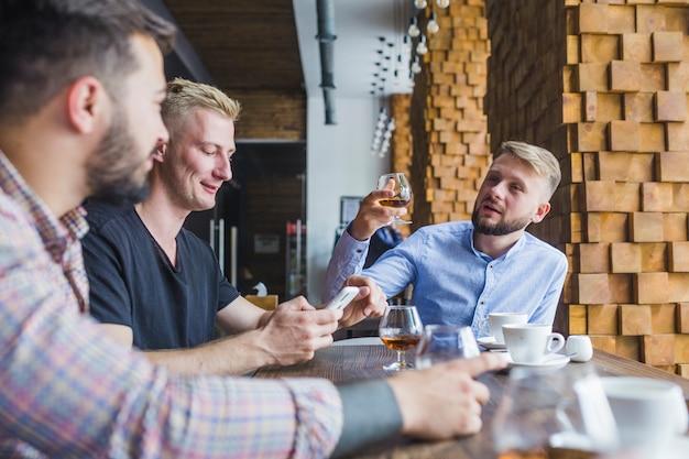 彼の友人とレストランでトーストを上げる男