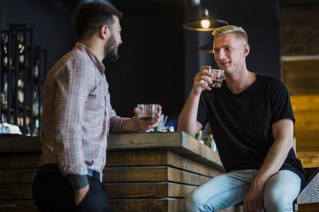 バーで彼の友人とウイスキーを飲む男