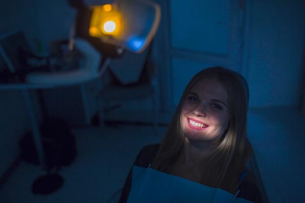 クリニックの女性の患者の歯の上に落ちる光