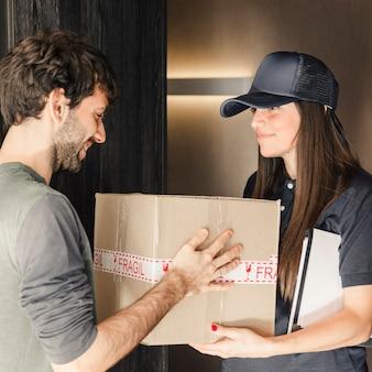 家庭で女性宅配業者から小包を受け取っている幸せな若い男