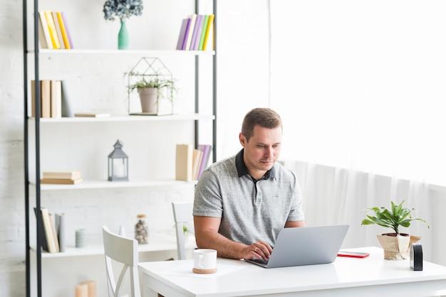 Человек, работающий на ноутбуке за столом