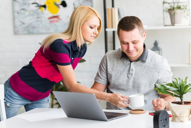 Женщина дает кофе мужу, работающему на ноутбуке