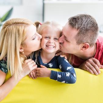 小さな娘にキスをする両親