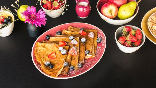 黒い背景に健康的な朝食とクレープ