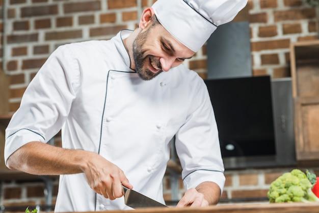 Улыбающийся мужской шеф-повар измельчения овощей
