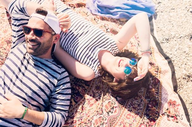 毛布の上に横たわるサングラスを着ている若い恋人を笑顔
