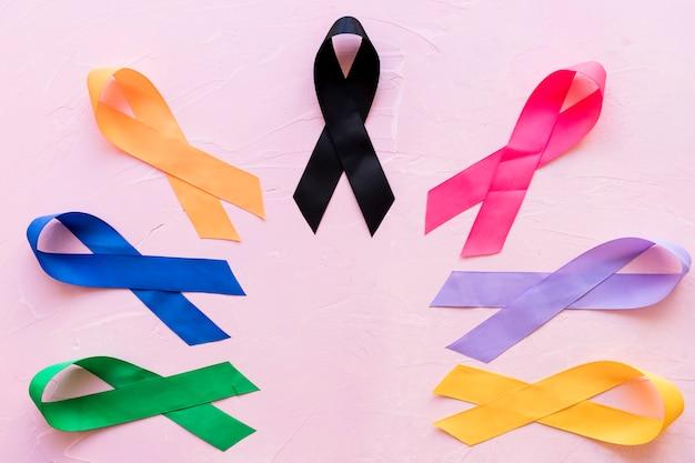 ピンクの背景に様々なカラフルな意識リボン