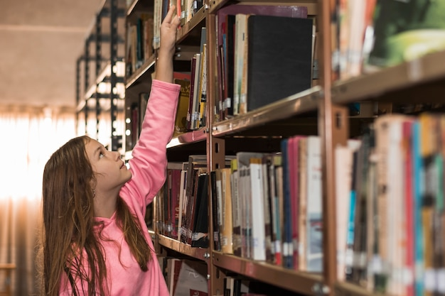 Девочка выбирает книгу из книжной полки